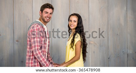 Smiling couple holding their hands and looking at camera against pale grey wooden planks - stock photo