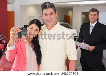 Smiling couple holding their new car key at new car showroom - stock photo