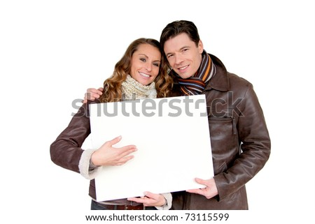 Smiling couple holding white message board