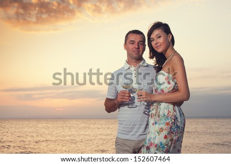 Smiling couple holding wineglasses during sunset on the beach of sea or ocean - stock photo