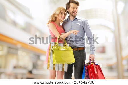 Smiling couple in a shopping mall - stock photo