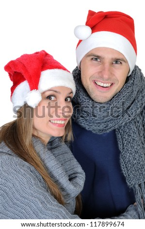 Smiling couple in Santa Claus Hats isolated on white - stock photo