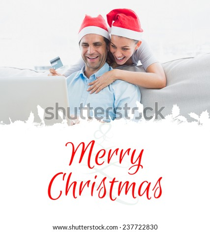 Smiling couple in santa hats shopping online with laptop against tree spiral - stock photo