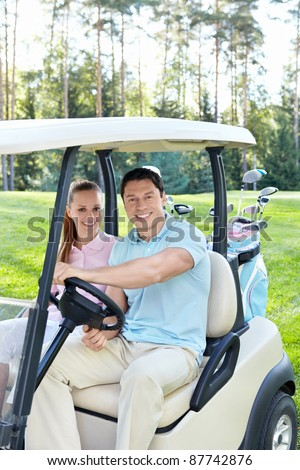Smiling couple in the car for golf