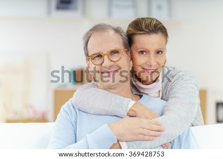 smiling couple in their fifties relaxing and embracing at home
