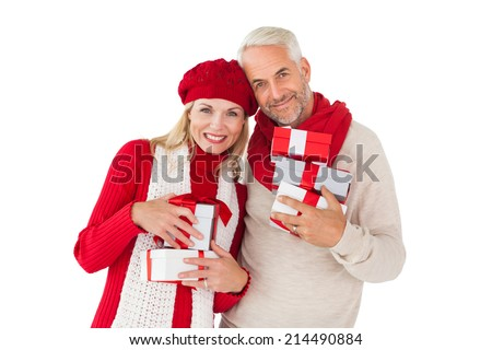 Smiling couple in winter fashion holding presents on white background - stock photo