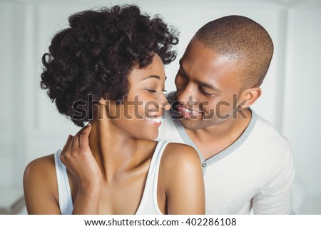 Smiling couple looking at each other at home - stock photo