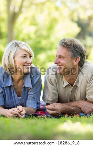 Smiling couple looking at each other while lying in park - stock photo