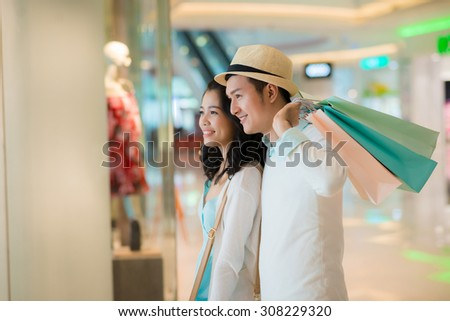Smiling couple looking at the showcase in the shopping mall - stock photo