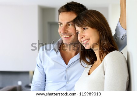 Smiling couple looking away by window - stock photo