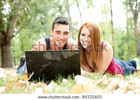 smiling couple lying on grass and looking in  laptop