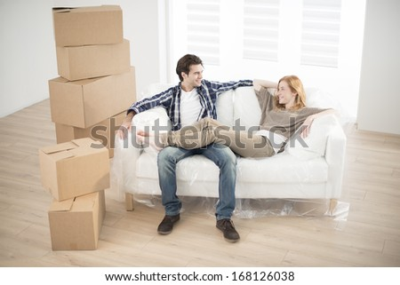 smiling couple lying on sofa in new home - stock photo