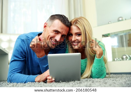 Smiling couple lying on the carpet and using tablet computer together