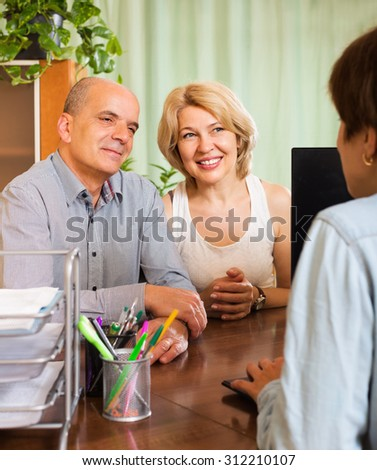 Smiling couple of pensioners talking with manager at notary's office