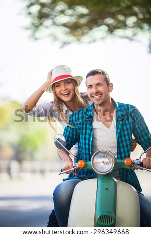 Smiling couple on a scooter outdoors