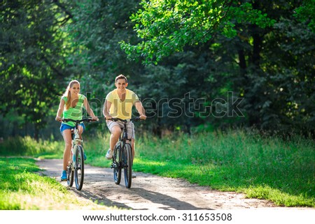 Smiling couple on bicycles in summer - stock photo