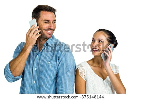 Smiling couple on phone call looking at each other on white screen - stock photo