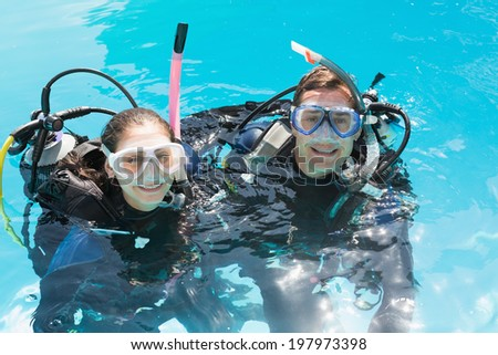 Smiling couple on scuba training in swimming pool looking at camera on a sunny day - stock photo