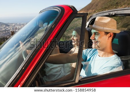 Smiling couple on their way to the beach in classy cabriolet - stock photo