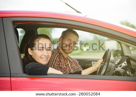 Smiling couple people in a red car - stock photo