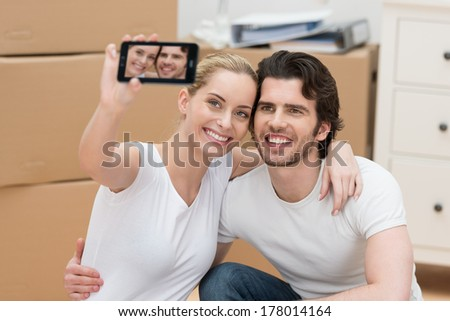Smiling couple photographing themselves on a mobile phone as the pose surrounded by brown cardboard cartons in their new home