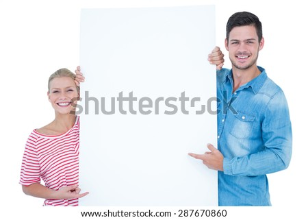 Smiling couple pointing at blank sign in their hands on white background - stock photo