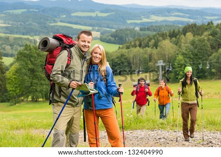 Smiling couple posing with hiking sticks and map on track - stock photo