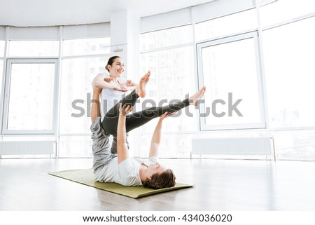 Smiling couple practicing acro yoga exercises in studio together - stock photo