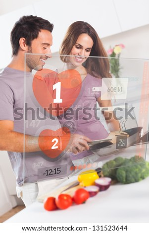 Smiling couple preparing dinner using futuristic interface in the kitchen at home