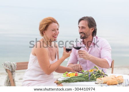 Smiling couple resting near by sea in the restaurant. People drinking delicious red wine from beautiful glasses.