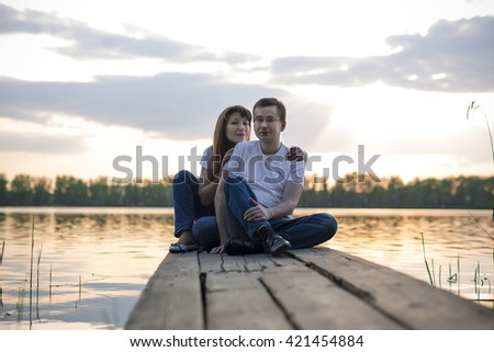 Smiling couple resting on the bridge on the shore of the lake at sunset
