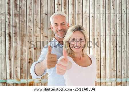 Smiling couple showing thumbs up together against faded pine wooden planks - stock photo