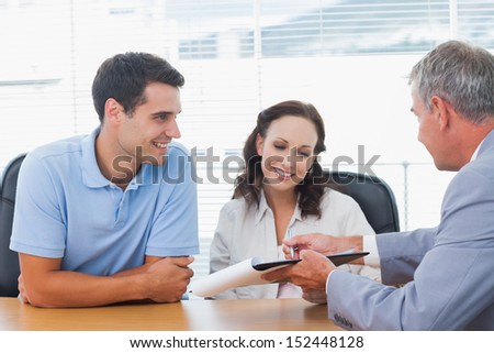 Smiling couple signing contract with real estate agent in bright office - stock photo