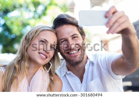 Smiling couple sitting and taking selfies at shopping mall