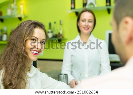 Smiling couple sitting at bar and female bartender pouring coffee. Focus on girl - stock photo