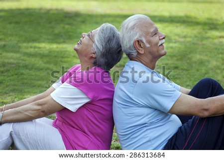 Smiling couple sitting back to back in a park