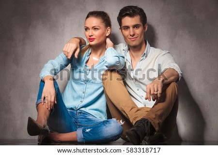 smiling couple sitting embraced on the floor, against studio wall