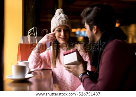 Smiling couple sitting in a cafe, the girl is thrilled about gift.