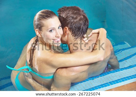 Smiling couple sitting in hotel swimming pool in summer - stock photo