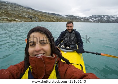 smiling couple sitting in kayak on lake Jostedalsbreen - Norway