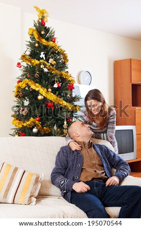 Smiling couple sitting on a couch at Christmas time