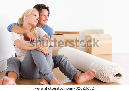 Smiling couple sitting on the floor looking away from the camera