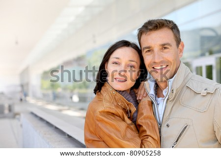 Smiling couple standing outside the airport - stock photo