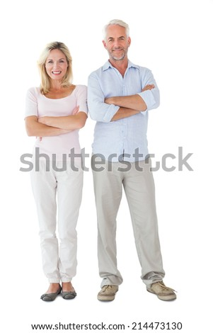 Smiling couple standing with arms crossed on white background - stock photo