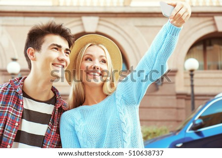 Smiling couple taking selfie by cellphone on the street