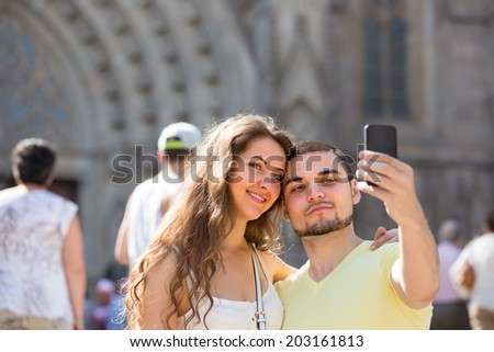 Smiling couple taking selfie in city at summer day