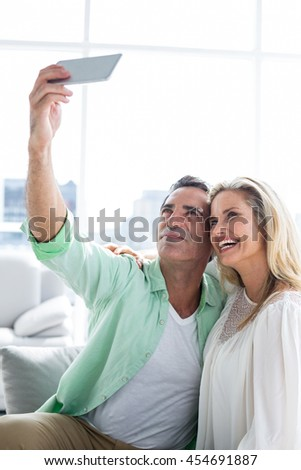 Smiling couple taking selfie while resting at home