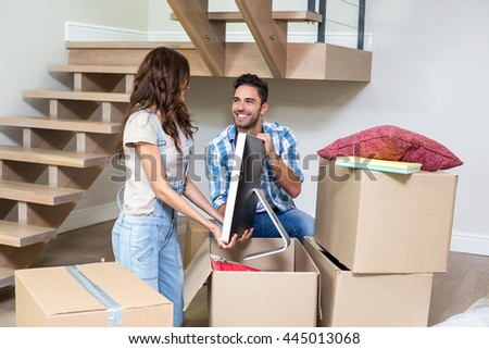 Smiling couple unpacking computer from cardboard box at home - stock photo