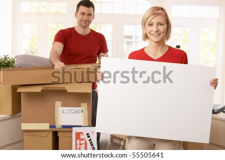 Smiling couple unpacking in new place, copyspace in blank poster. - stock photo