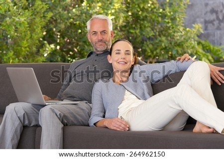 Smiling couple using a laptop lying on a sofa. - stock photo